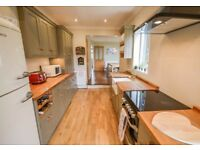 Full shaker style kitchen with wooden work surfaces - including: taps, cooker, fan and dishwasher.