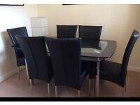 Black glass dinning table with six leather chairs
