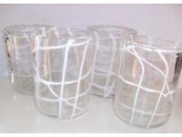 HANDMADE BLOWN GLASS TUMBLERS OR CANDLE HOLDERS WITH WHITE SLIP DECORATION.