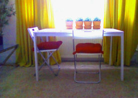 White IKEA table 70cm by 150cm. 2 white chairs. Used 10 times for ten minutes
