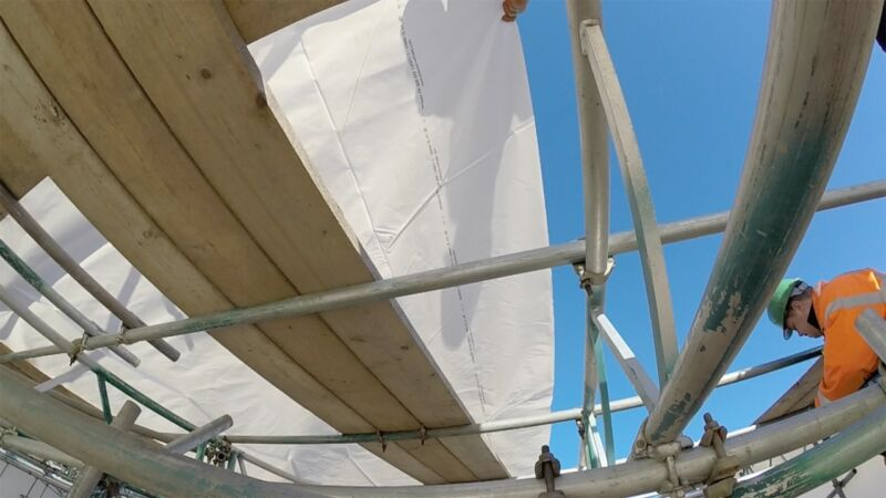 Unfolding the shrink wrap sheeting across the temporary roof