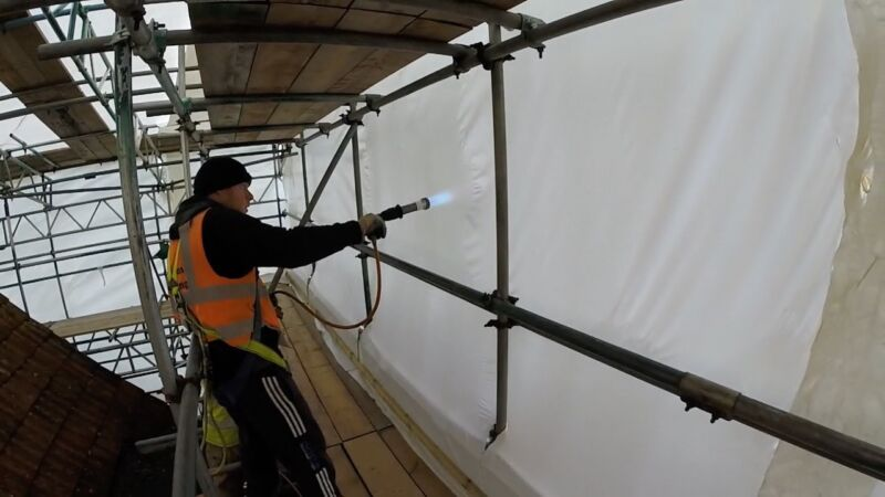 Heat shrinking the sheeting around the scaffold sides using a hand held propane gas hot air gun