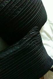 Two black satin pleated plump cushions.