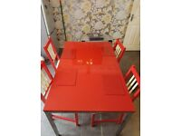 Red gloss dining table and 4 x red/cream hand painted chairs. Table approx 53 x33