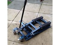 Motorcycle hydraulic lift as new will lift a Harley,locking wheels and handle for moving about.