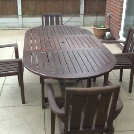 Teak table and four chairs.Table has centre section that folds in to make it smaller.