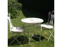 Bistro cafe set wrought iron set table and two chairs.two padded chair cushions