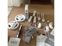 White Nintendo wii console 2 wheels 2 num chucks and various other parts, games available
