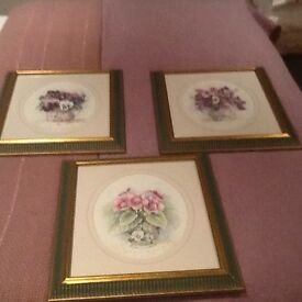 Three middle size floral pieces of art work