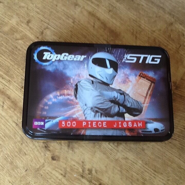 A NEW & UNOPENED BBC TOP GEAR THE STIG JIGSAW PUZZLE IN A TIN WITH 500 PIECES.