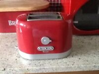 A TOASTER A BREADBIN AND A RECIPE HOLDER ALL IN RED