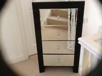 Mirrored and black tallboy chest of drawers in good condition except for a small chip on the end