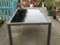 Garden table with glass top and rattan effect edges and legs