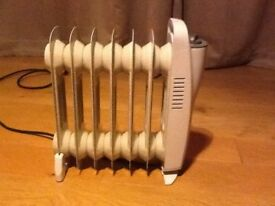 Small Oil Filled Electric Radiator. Measures 350x350x100mm and has variable heat control.