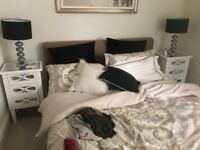 2 white bedside tables and lamps