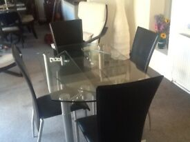 Extending circular glass table with silver look legs and four leatherette chairs