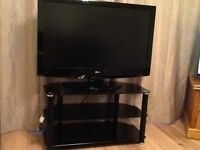 """LG flat screen television 42"""" with black glass stand."""