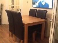 Extending oak dining table and four brown leather chairs