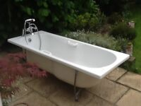 A white bath and a set of taps with a shower head