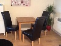 4 seater wooden table with 3 black leather effect scroll chairs