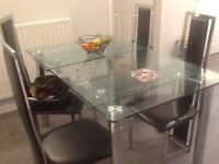 Dining table and 4 chairs. Clear glass extendable top.
