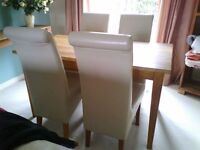 Solid oak dining table and 4 high back cream leather chairs