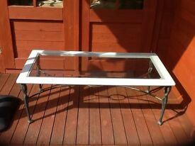 Glass topped coffee table set in wood with metal legs and frame. Height 40 cm lgth 110cm 55cm wide