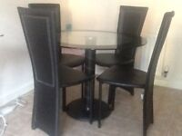 Small round glass top dining room table with four chairs in excellent condition.