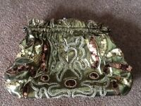 A BRONZE/GOLD COLOUR CARPET STYLE CLUTCH BAG WITH METAL CLASP & BEADING PATTERN