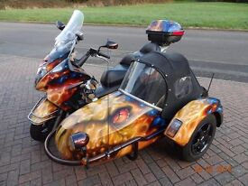 Honda silver wing scooter with side car.