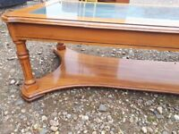 Solid wood coffee table with wicker and glass top.