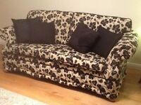 Suite comprises 3 seater settee and 2 armchairs in beige with black leaf patterned fabric.