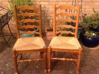 Two wooden high back chairs with rattern seats