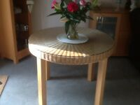 Round glass topped dining table, cane top, oak legs