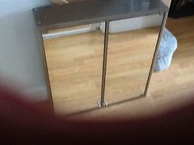 Stainless steel Bathroom cabinet with mirrored doors.