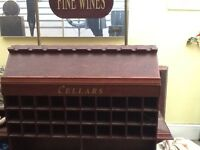 A very large wooden wine rack it holds a 100 bottles and has shelving for crates etc.