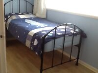 Single bed with mattress in black wrought iron.