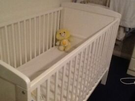A white baby cot in a very good condition