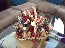Large dried floral arrangement in wicker basket.