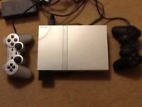 Play Station 2 silver slimline model and 2 controls