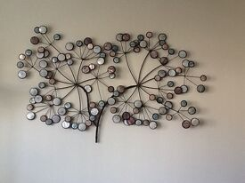 Metal wall art in pale blue and beige.