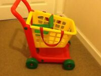 Toy shopping trolly with foldable dolls seat and removable basket