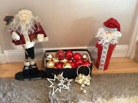 Red and gold Xmas tree decorations and two father Xmas figures