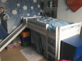Child's cabin bed with ladder/slide and curtain for storage underneath