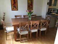 Oak dining table and 8 chairs with covers, all excellent condition