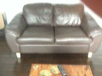 Two matching brown faux leather sofas