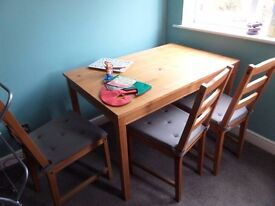 IKEA PINE TABLE AND 4 CHAIRS WITH GREY CUSHIONS