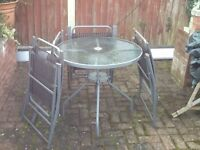 Garden glass top table and 4 chairs,all metal framed.
