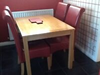 Table and 4 faux leather red chairs