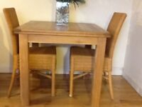 Almost new dining table and two wicker chairs